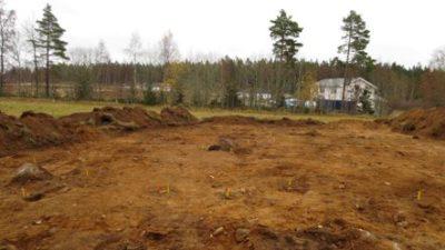 En schaktad yta med röda pinnar i jorden. I bakgrunden syns en gräsyta samt ett hus med skog bakom.