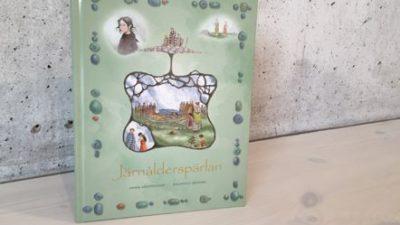 Bild av boken mot en grå vägg. Omslaget har titeln Järnålderspärlan mot en grön bakgrund. Akvareller föreställande barn i forntida klädsel. I mitten av bilden en illustration av en dåtida begravning. Allt är inramat av rader av pärlor.