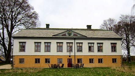 Bild på Rosenlunds herrgårdspark. En gul och vit byggnad.