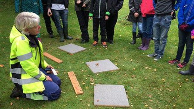 En arkeolog sitter på knä på gräset med stenplattor framför sig. Runt henne står en grupp med barn.