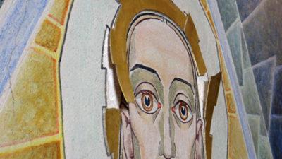 Ansikte målat på vägg. håret i guld lossnar från väggen.