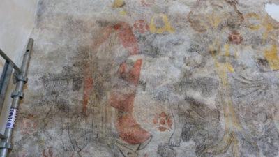 Vägg med målning i grå, gula och röda färger.