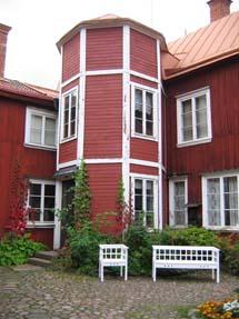 Ett rött trähus med en rund utbyggnad.