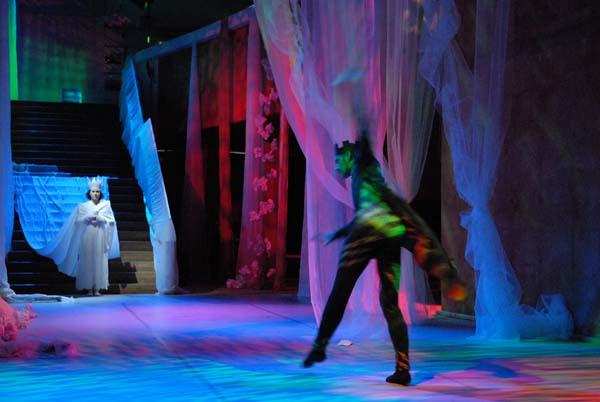 En människa dansar i neonljus.