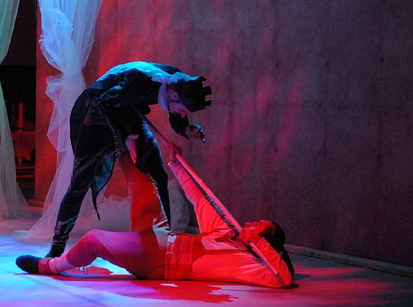 En man ligger ner på en scen med en pinne i handen. Över mannen står en annan man.