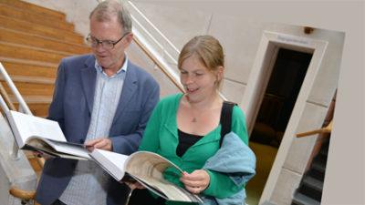 Två personer som tittar i boken.