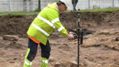 En man står i en jordgrop med ett verktyg. Bakom honom syns höghus och en sjö.