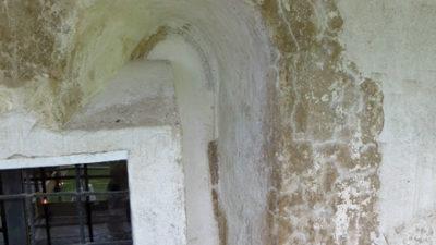 Mörkt fönster i en putsad och kalkad vägg.