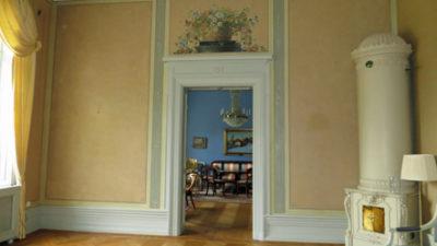 Vägg med dekorationsmålning. Till höger i rummet står en vit kakelugn.