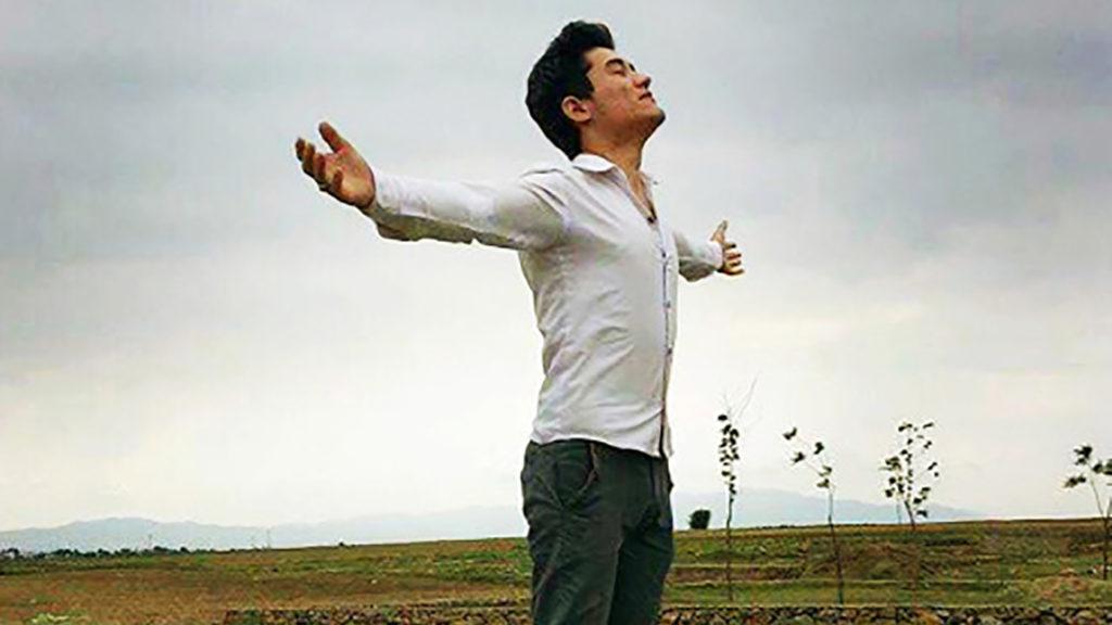 En person vänder ansiktet mot himlen och håller ut händerna.