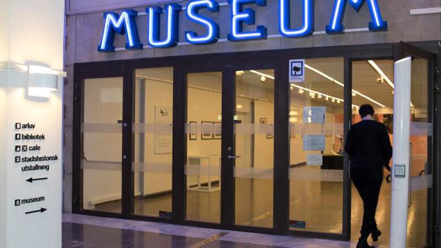 Entrédörrar med neonskylt ovanför med texten MUSEUM.