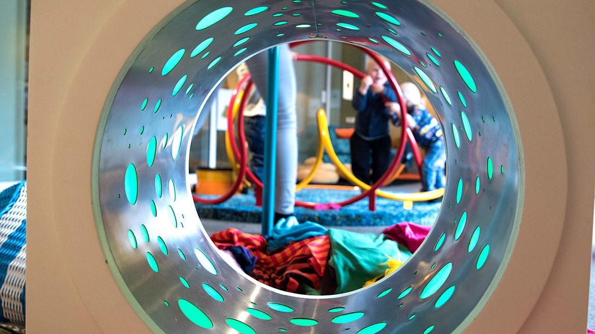 En tunnel med blåa prickar. På andra sidan tunneln ser man leksaker.