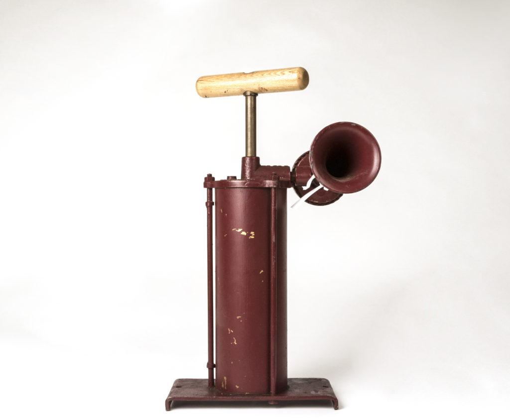 Gjutjärnsredskap med pump och signalhorn. Färgen är rostbrun.