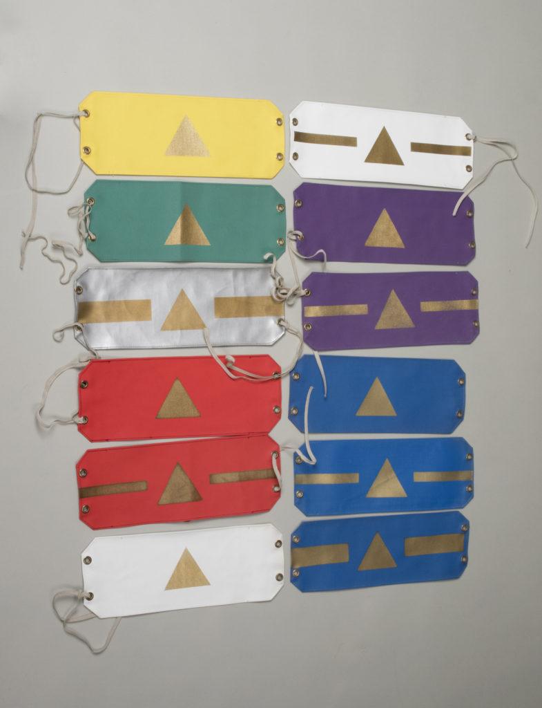 Avlånga armbindlar av galon med gummiband i vardera kortände. De är i olika färger: gul, grön, silver, röd, vit, lila och blå. De har tryckta geometriska figurer: triangel och rektangel i kombinationer. Tryckfärgen är guld.