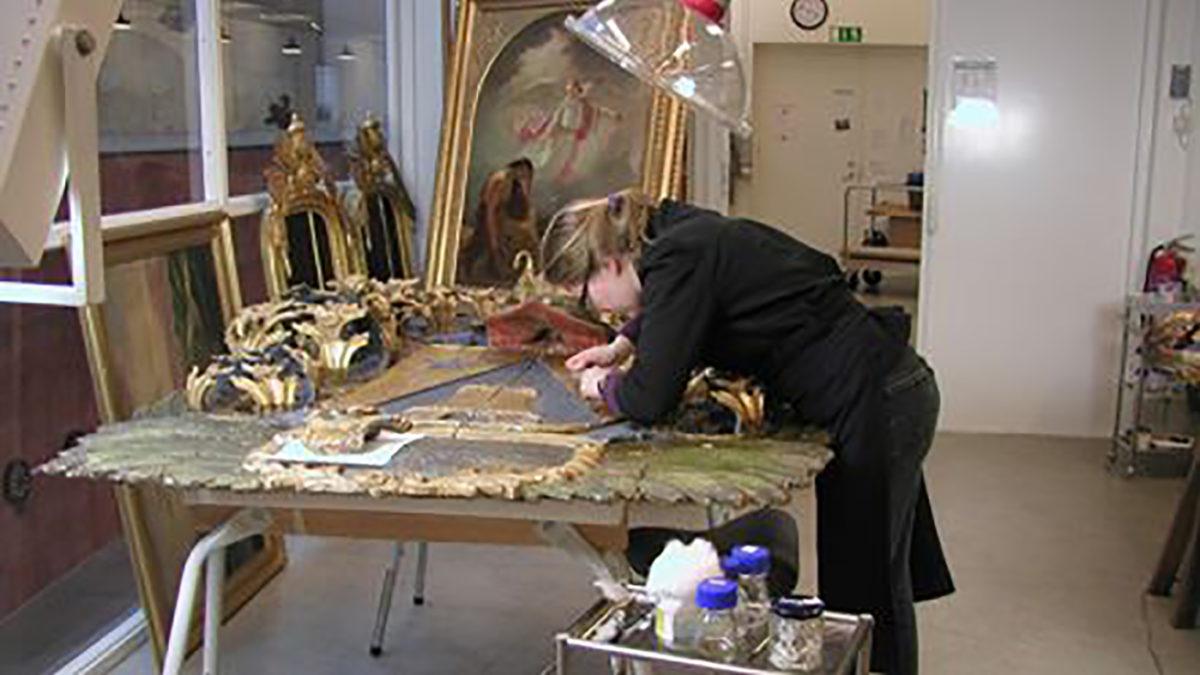 En konservator står böjd över en målning vid ett bord..