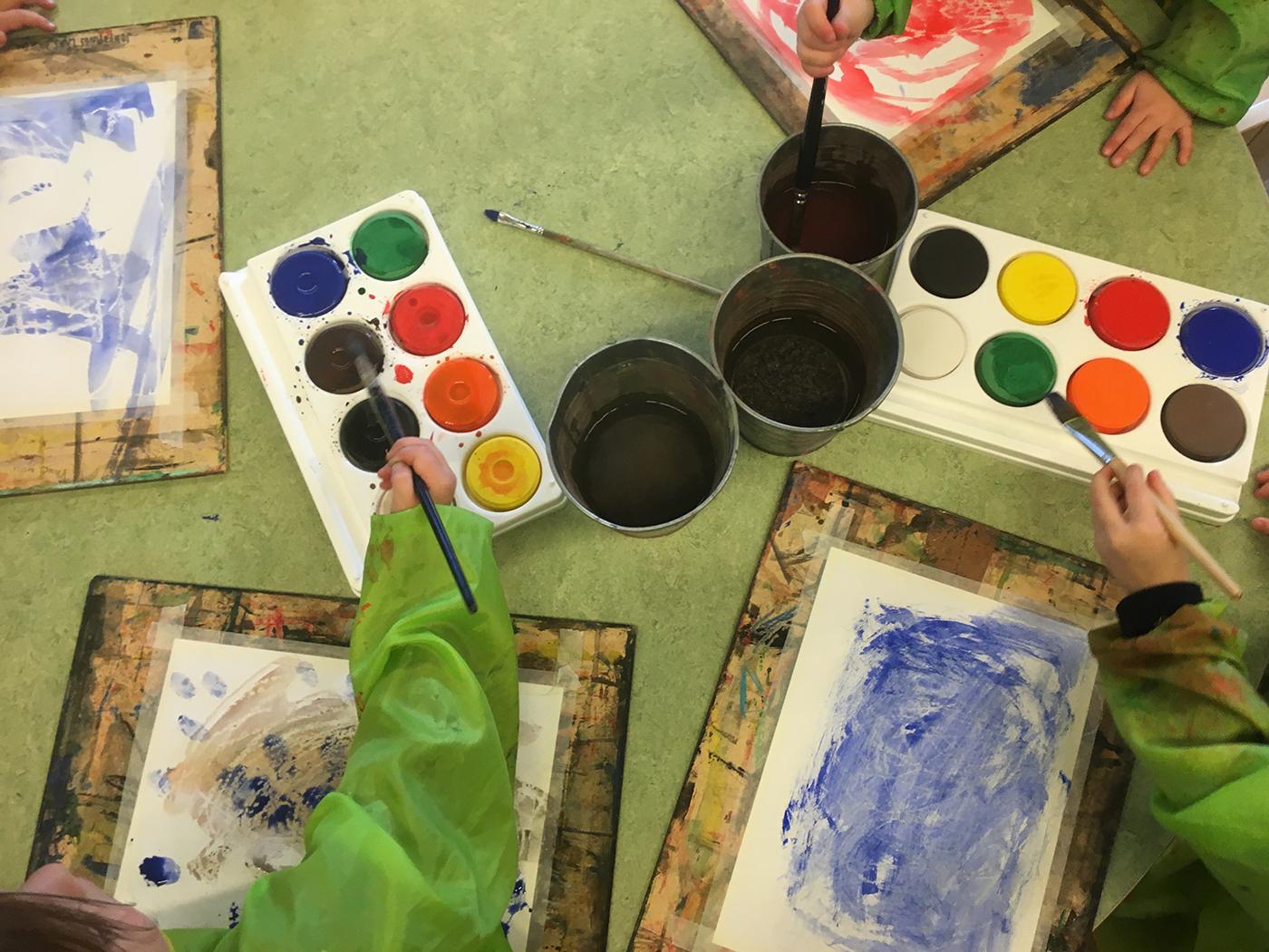 Barnhänder som målar med vattenfärg.