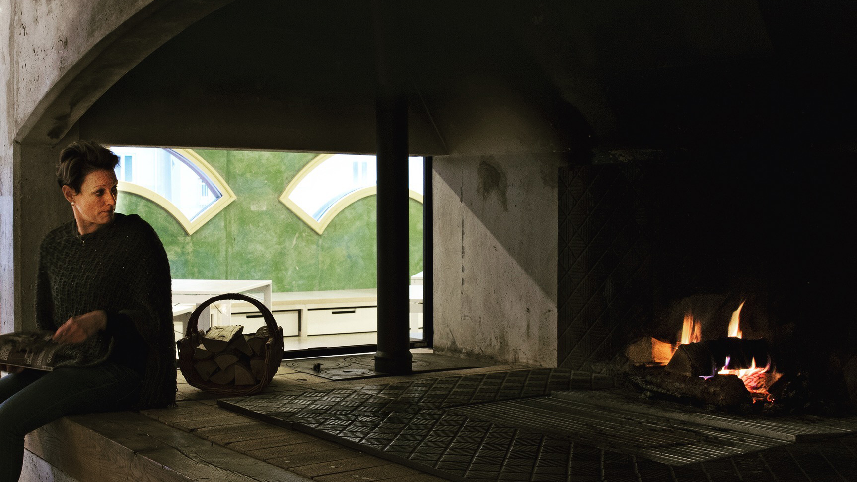 En person tittar in i elden i den öppna spisen.