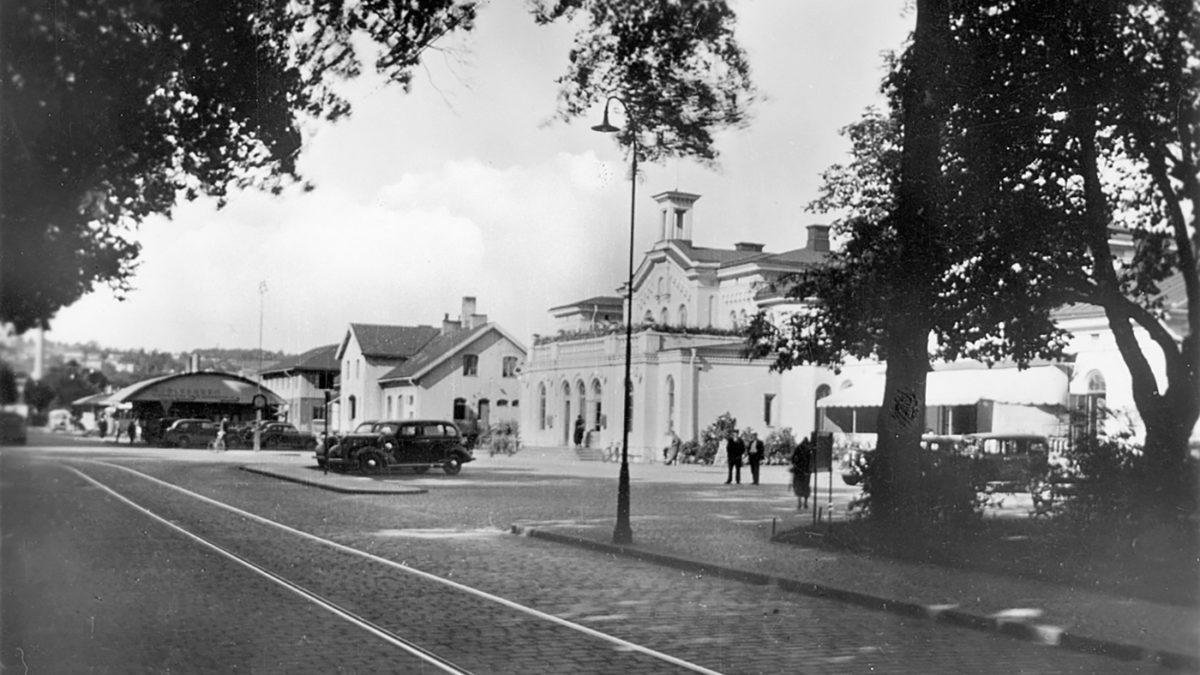 En järnvägsstation med spårvagnsrälsar på gatan framför..