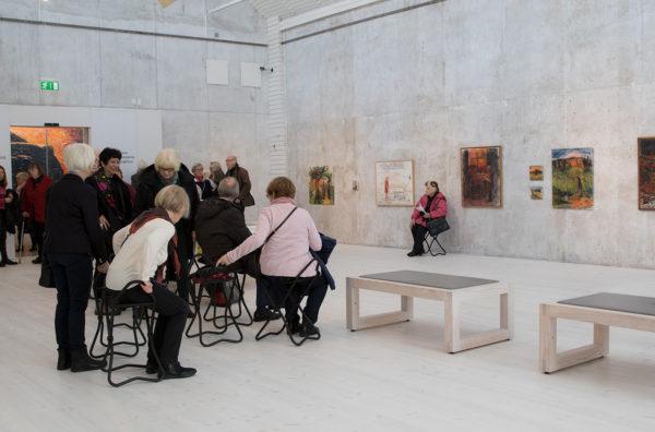 Stor, vit sal, vernissagetillfälle på Jönköpings låna museum. Människor som sitter och står.
