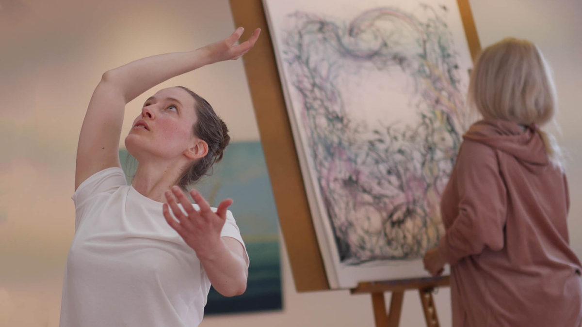 En person dansar framför ett staffli med färgglad målning på som arbetas med
