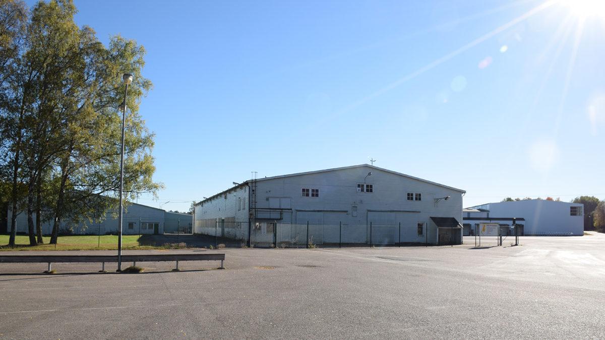 Vit industrilokal på asfaltsplan