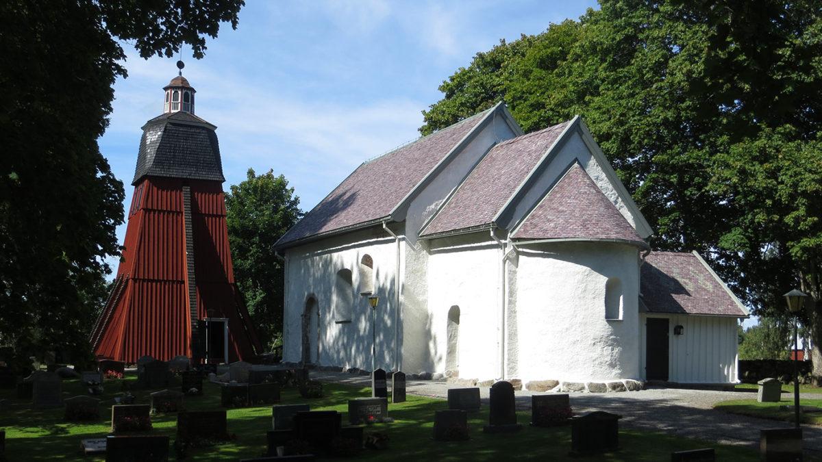 Vit kyrka med kyrkogård framför