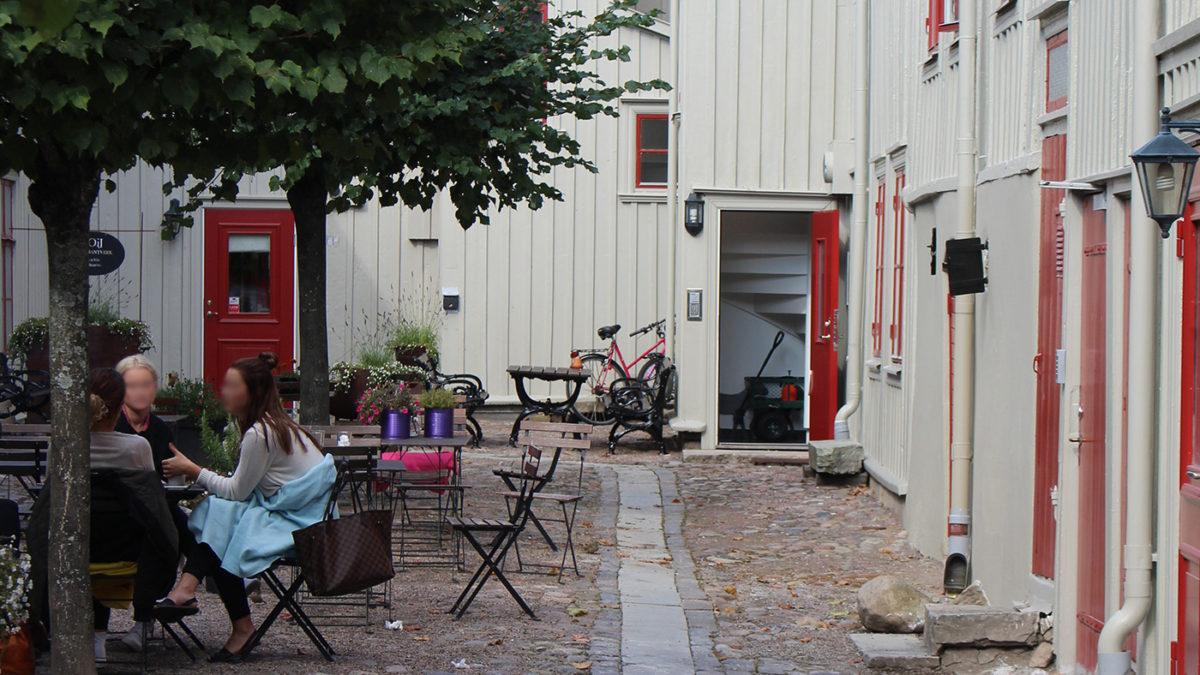 Innergård med hus med röda dörrar samt träd och kullerstensgång