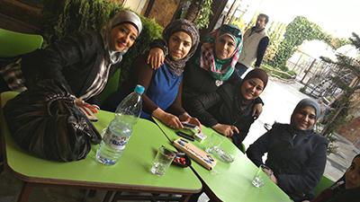 Fem kvinnor sitter kring ett bord och ser in i kameran.