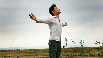 En man står på en stenmur framför öppet landskap med öppna armar.