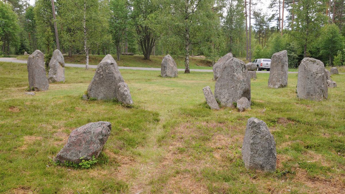 Gamla gravstenar på en gräsmatta i skogskanten.