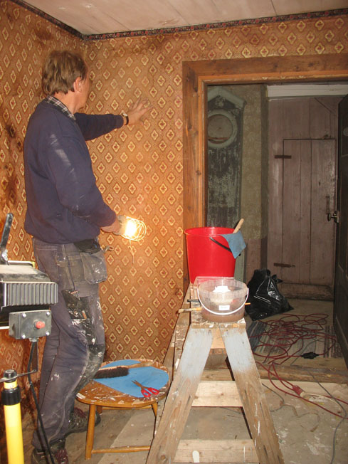 En man undersöker en tapetserad vägg.