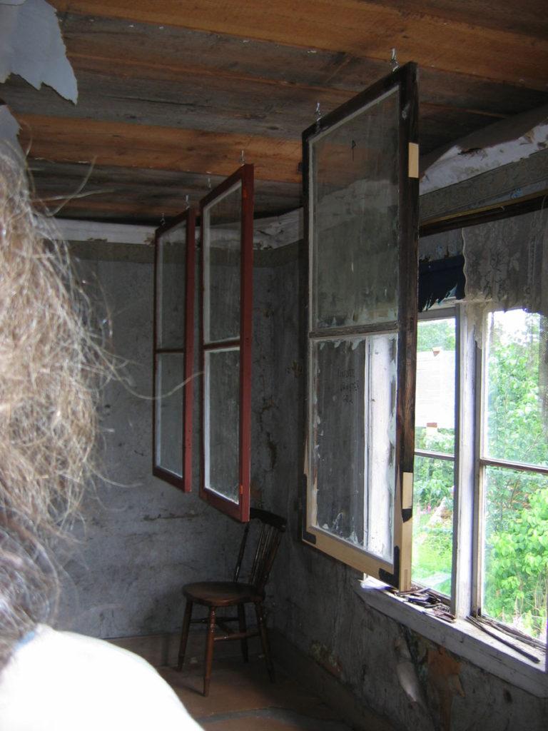 Fönsterbågar hänger från taket, målning pågår.