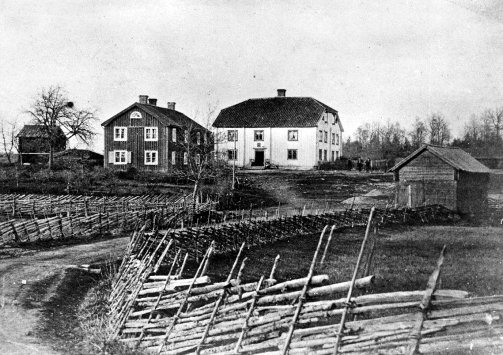 Två äldre hus längs en väg hägnda med gärdsgård.