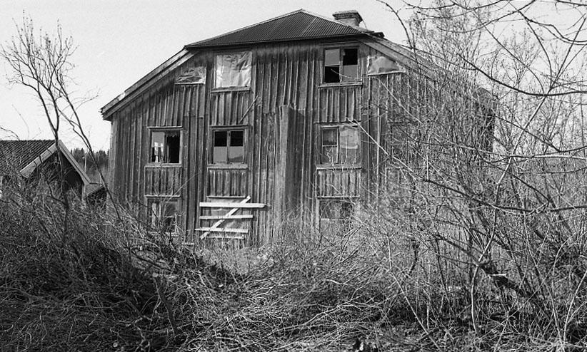 En gavel på ett hus med trasiga fönster.