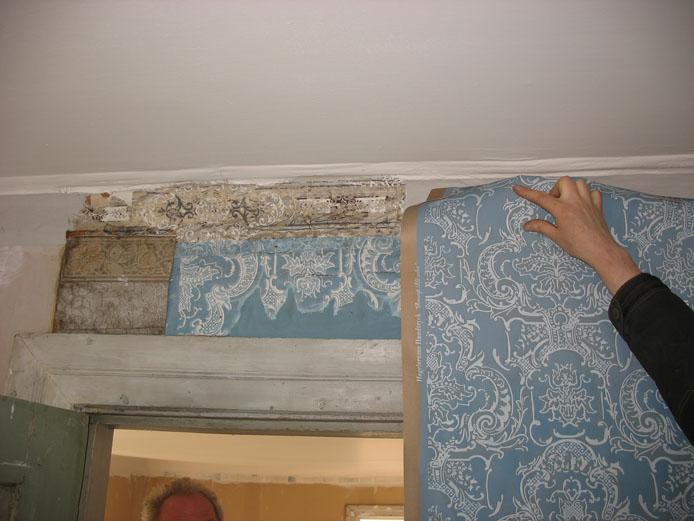 En tapetrulle hålls som jämförelse mot en äldre tapetbit på väggen.