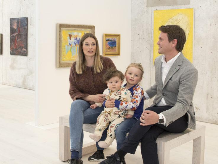Två vuxna och två barn sitter på en bänk framför en vägg med konst.