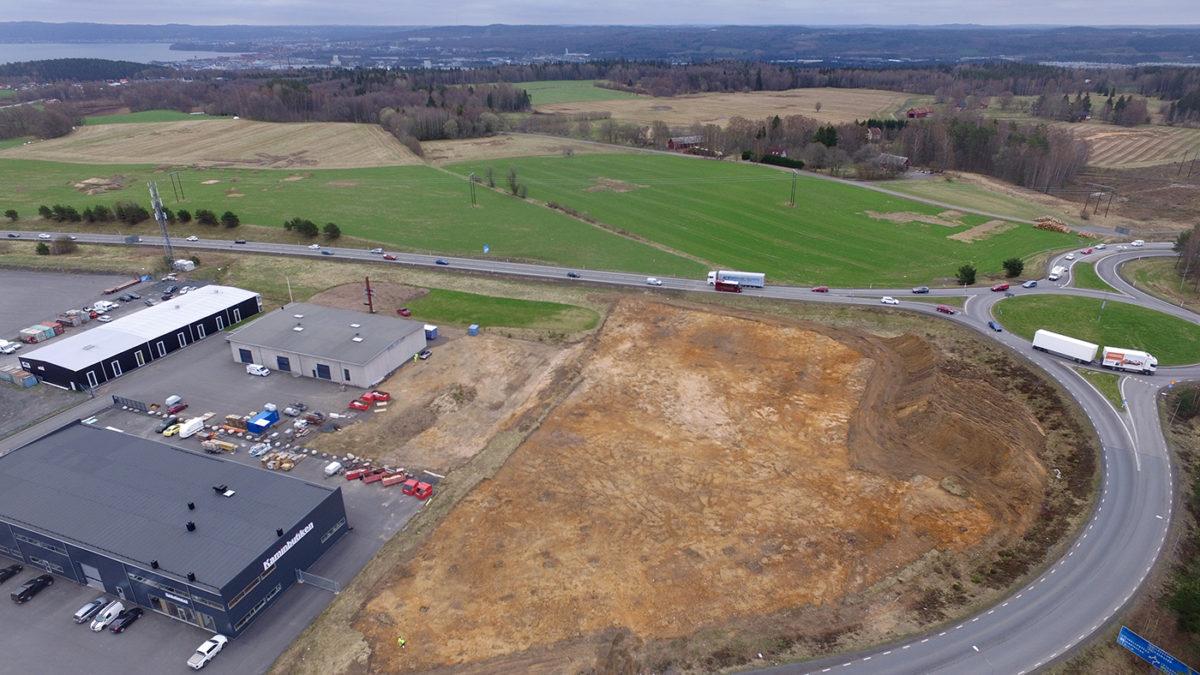 Drönarfoto visa uppifrån avbanad stor yta omgiven av bilväg och industribyggnad.
