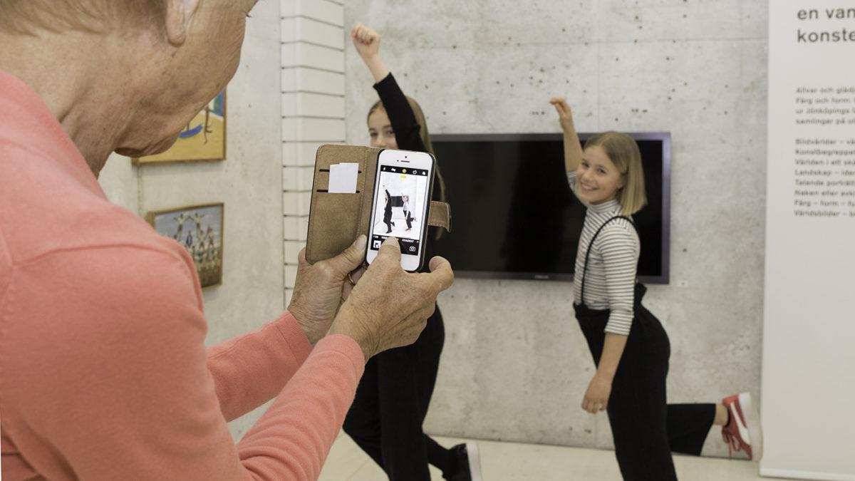 Två barn dansar. En vuxen tar bild på dem.
