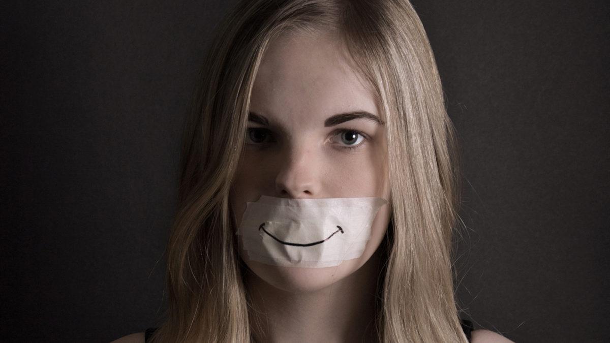 Tystnad talar av Lina Elmebro. En flicka med en tejp över munnen där det är ritat en glad min, men flickan ser allvarlig ut.