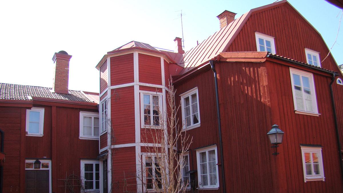 Röd träbyggnad med vita knutar och fönsterkarmar.