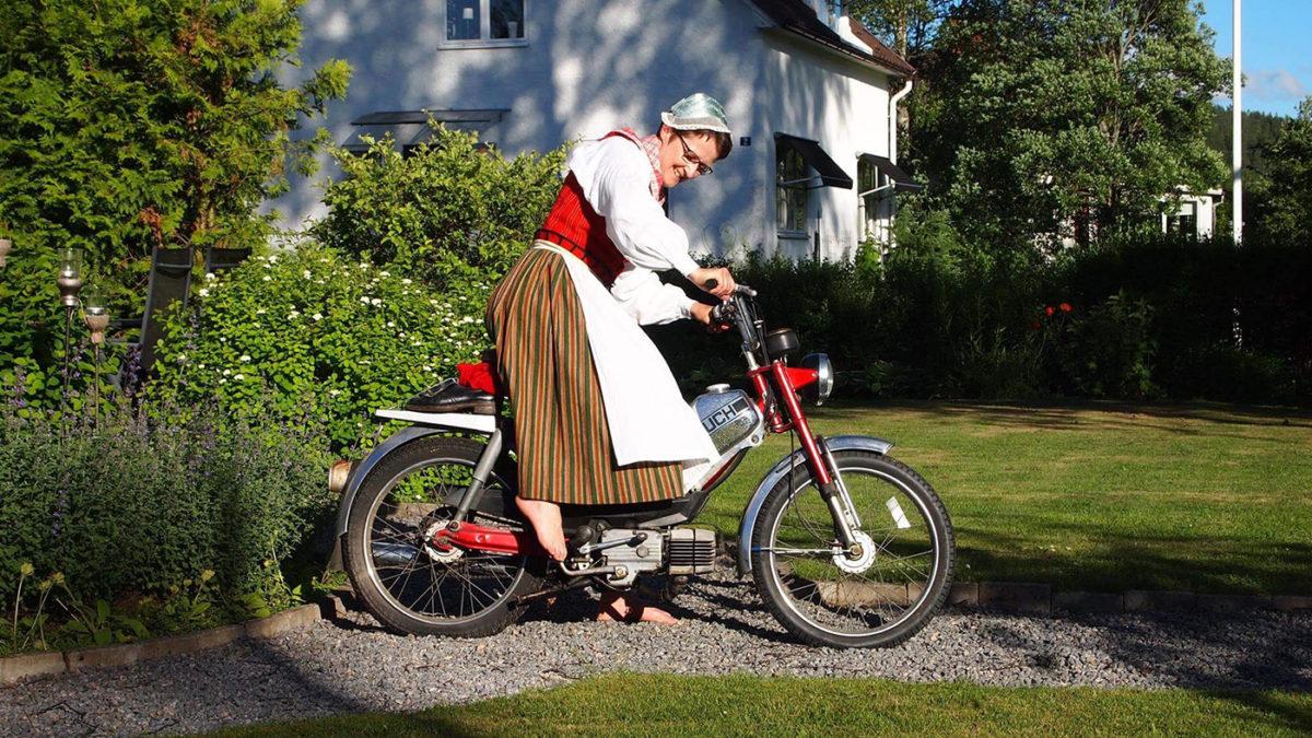 En person i folkdräkt kickar igång en moped.