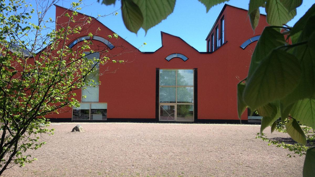 Museibyggnaden, terracottafärgad och sågtandat tak.