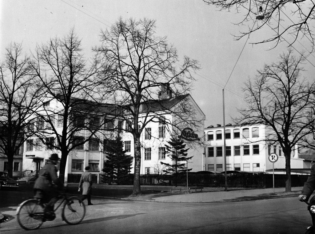 Fabriksbyggnad bestående av flera huskroppar i flera våningar, och vitfärgad fasad.. Fabriken är belägen vid en gatukorsning. En cyklist och en fotgängare syns i nedre vänstra hörnet.
