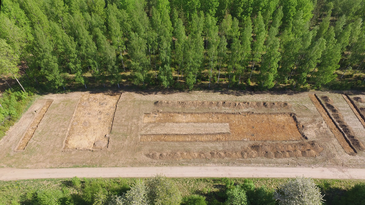 Ett uppgrävs landområde intill en skog. Drönarbild.