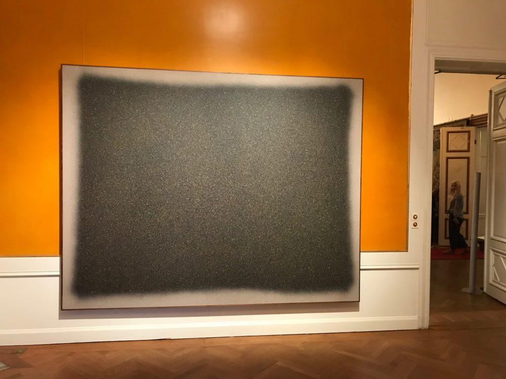 En stor spraymålning av konstnären Paul Fägerskiöld i svart och grått hänger på en varmt gul vägg.