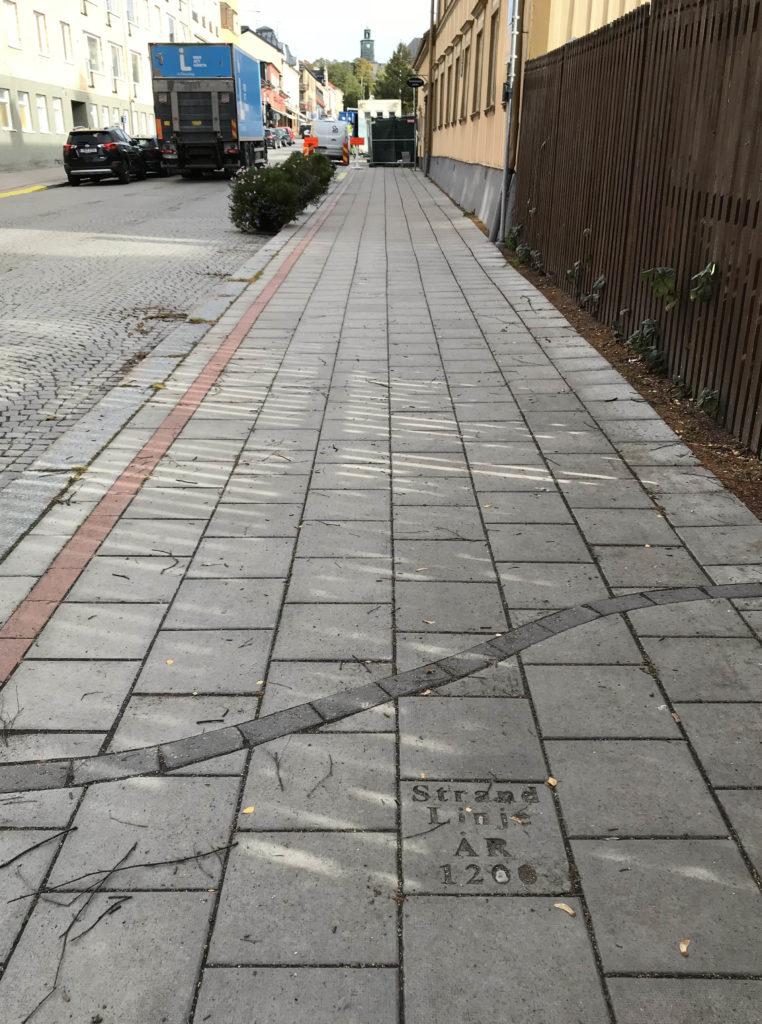 Bilden visar en trottoar där man har markerat 1200-talets strandlinje i stenläggningen med stenar i en avvikande färg samt en platta med text.