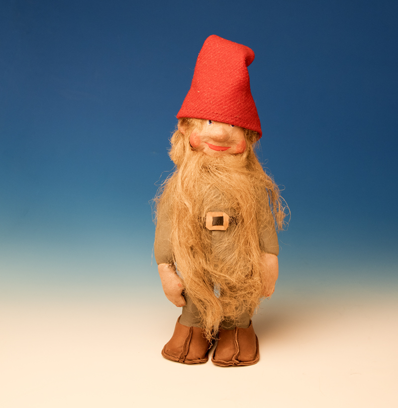 Jultomte-docka med skägg, gråa kläder och röd luva, skärp och skor av skinn.