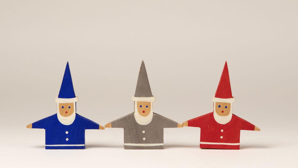 Tre jultomtar stående bredvid varandra, målade i respektive färg blått, grått och rött. Formen är en platt figurskulptur av trä med endast överkropp. Armarna är utsträckta åt sidorna. På huvudet sitter en upprättstående spetsig mössa.