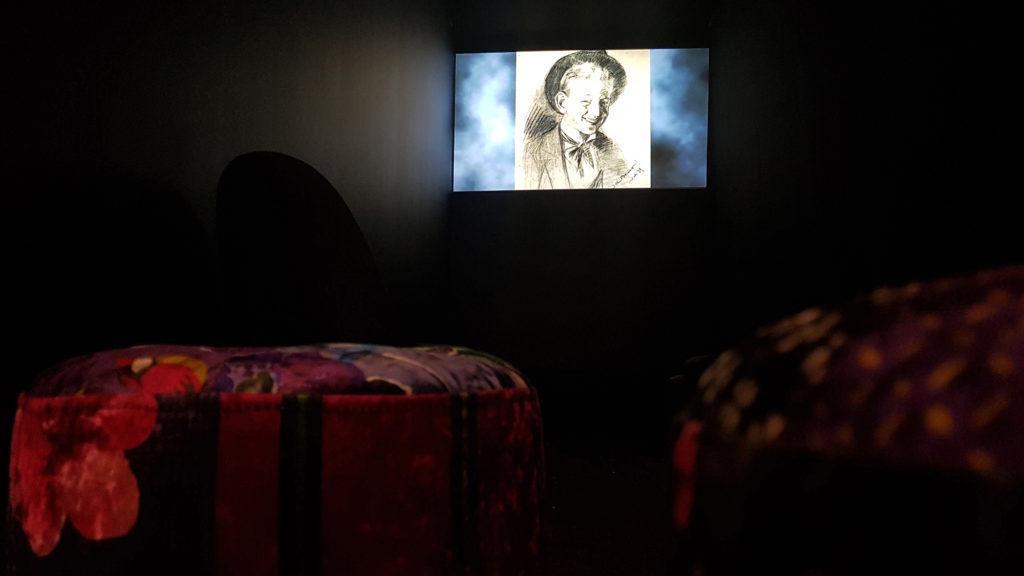 Ett mörkt rum med en skärm längst fram som visar en film. I rummet anas mjuka puffar i varma färger.