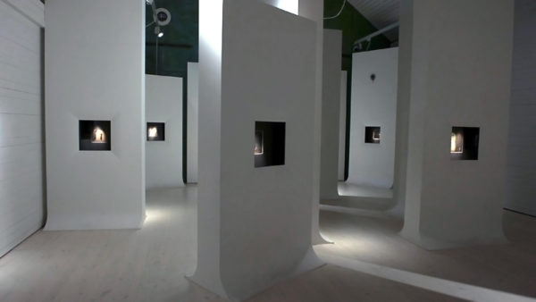 Ett dunkelt rum med flera vita väggar där bilder är infällda i väggen.